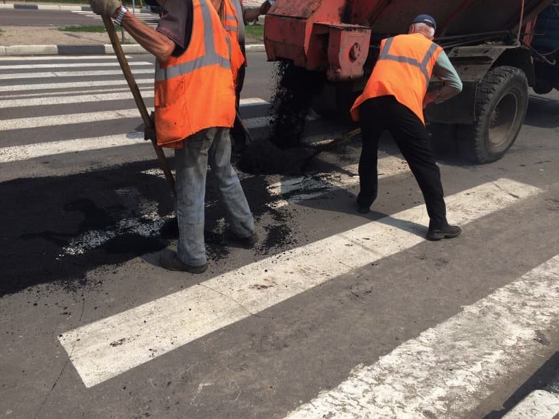 Paving Contractors Repairing a Pothole on the Road in Maryland
